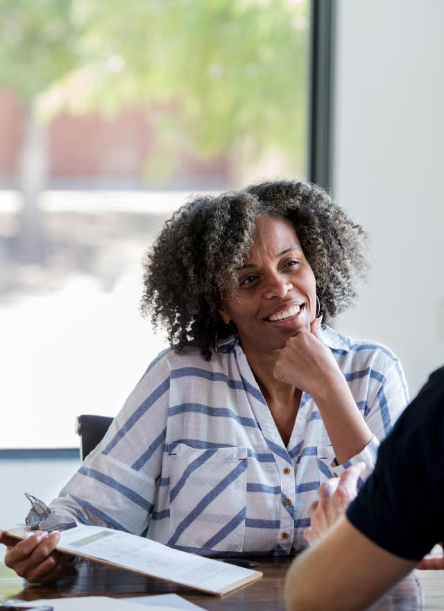 Mature businesswoman talks with male colleague stock photo
