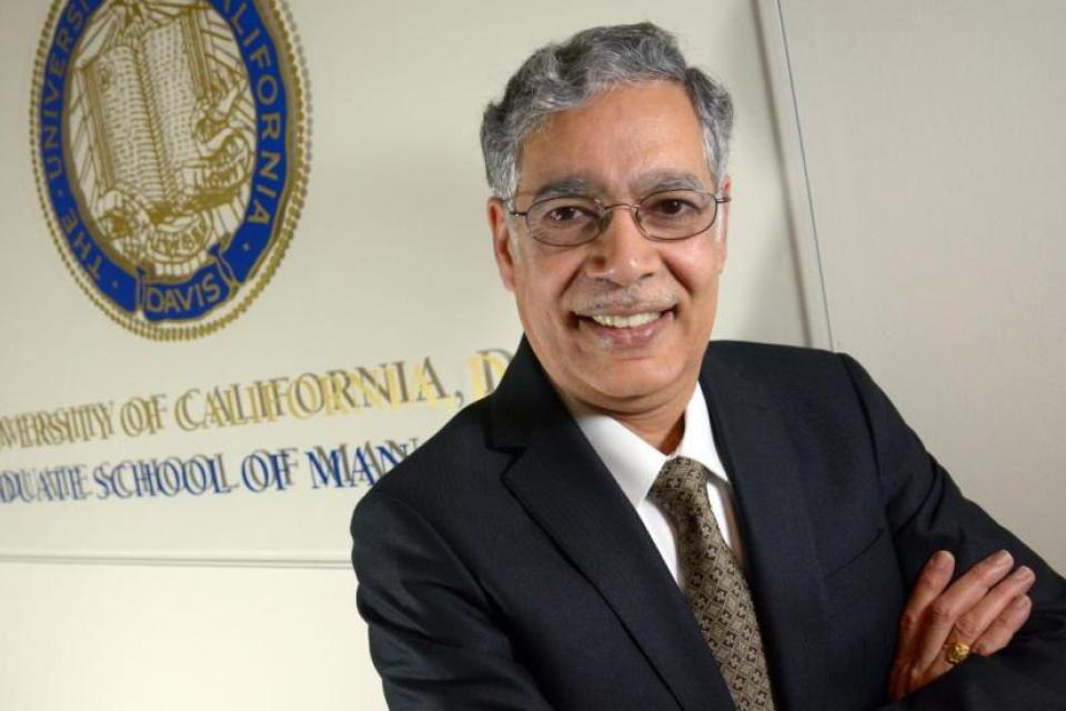 Dean Unnava posing in front of the UC Davis seal