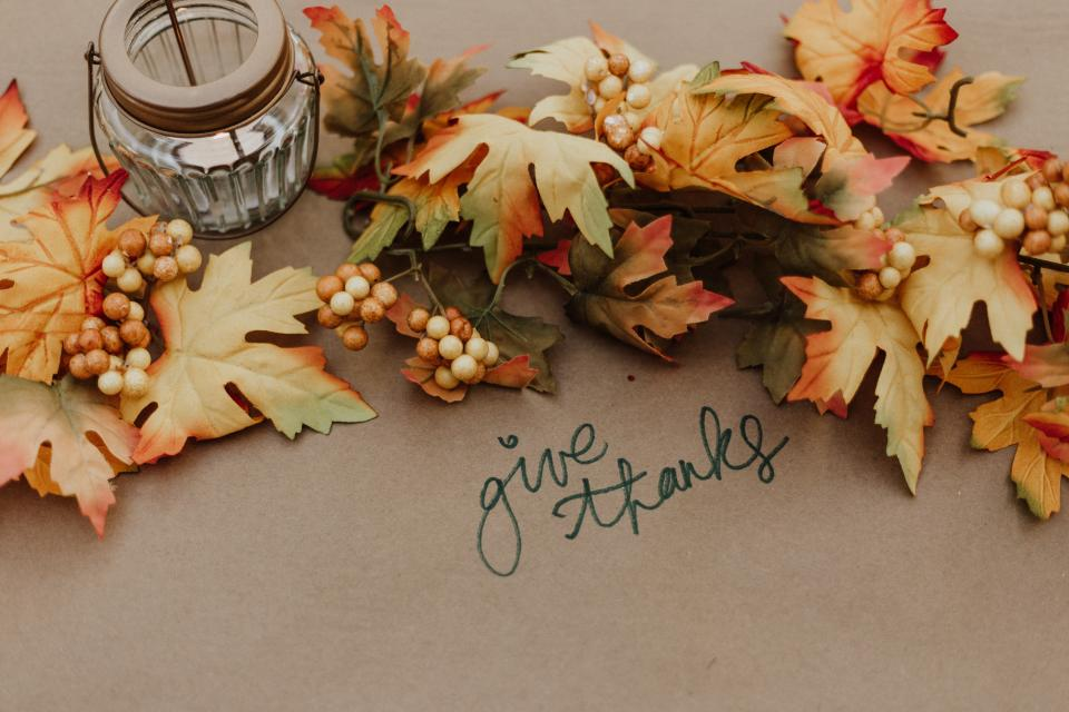 Give thanks written on table with fall leaves